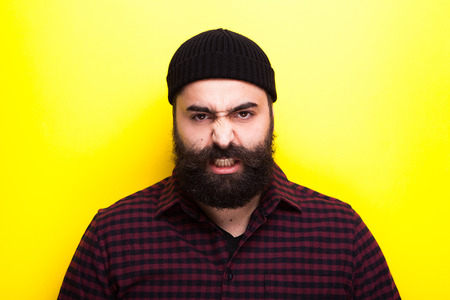 Portrait of hipster man with a long beard on a yellow background