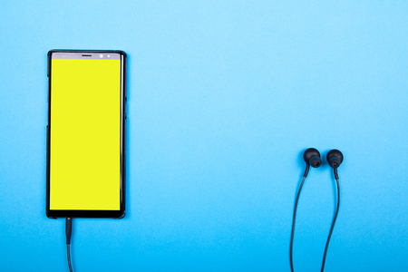 Top view of smartphone with yellow screen connected to headphones on blue background Stock Photo