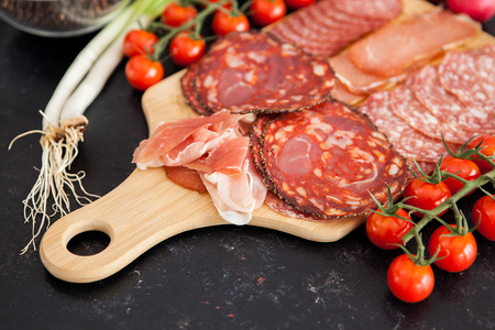 Close up on different meat appetizers on wooden board Stock Photo