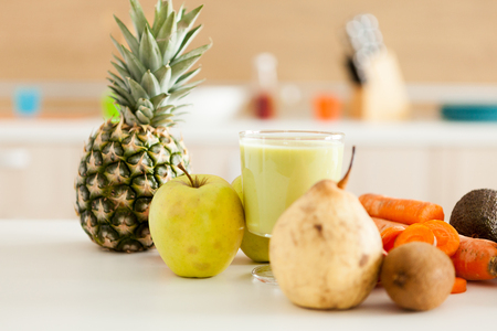 Detox juice next to fruits and vegetables at the kitchen