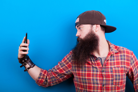 Bearded hipster with a hat taking a selfie on blue background