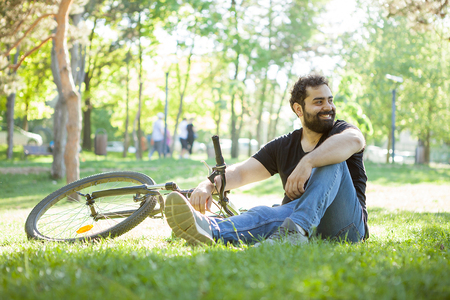 Man next to his bicycle resting on the grass in the park Stockfoto