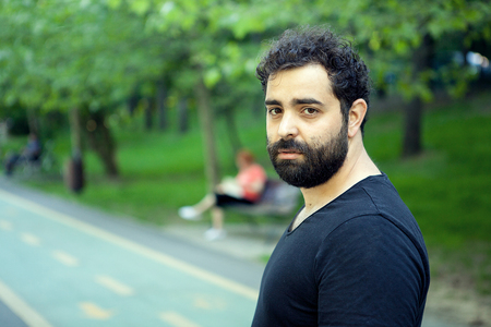 Portrait of young bearded man looking at the camera in the park Foto de archivo