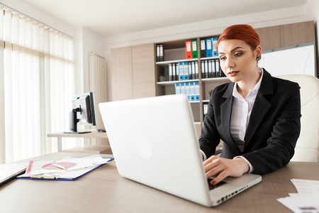 Close up wide angle image of businesswoman in her office working 版權商用圖片