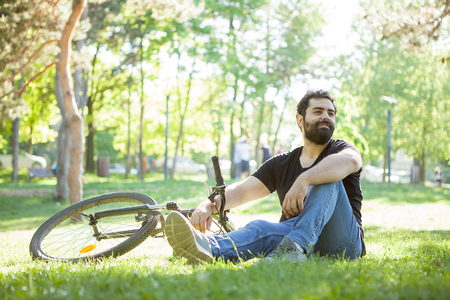 Bearded man next to his bicycle resting on the ground in the park