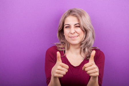 Blonde woman showing thumbs up to the camera on purple background