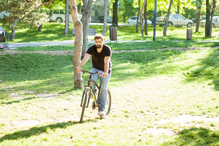Young man riding a bicycle in the park in summer Stock fotó