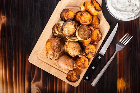 Top view of fried chicken next to grilled sweet potatoes, quash and sour cream souce on wooden background