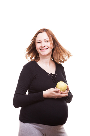 Pregnant woman smiling to the camera while holding an apple in her hands. Isolated on white background