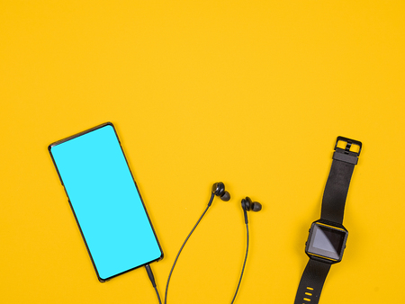 Flat lay top view of smartphone and smartwatch. Design and concept. Orange background