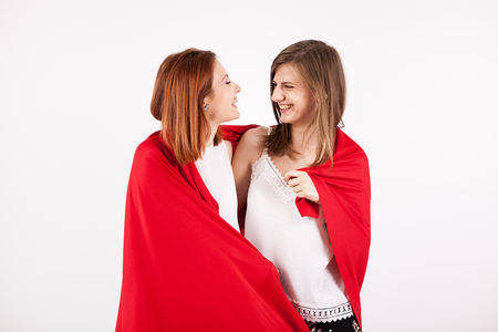 Two beautiful female friends covering them self with a red blanket in studio photo over a white wall