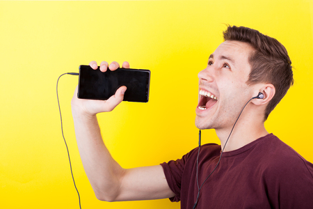 Joyful man with headphones in ears singing in the phone like it is a microphone. Yellow backgorund. Studio photo Banco de Imagens