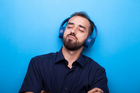 Young man listening to music through headphones on blue background