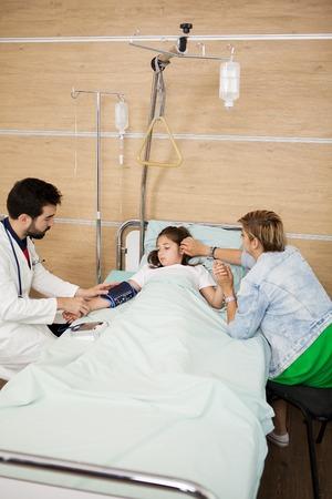 Médecin prenant la tension artérielle de son patient dans la chambre d'hôpital