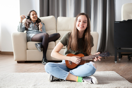 Two sisters, the younger one is playing a small guitar in front at the other is singing in the back on the couch