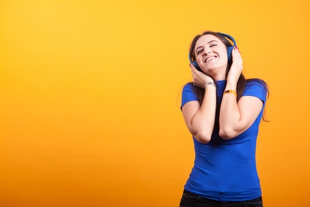 Beautiful youg woman listening music with her headphones on yellow background Stock Photo