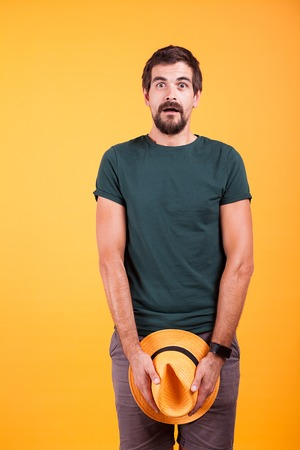 Surprised dressed man covering his parts with a hat on orange background