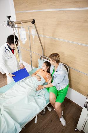 Médecin visitin patient fille dans la chambre d'hôpital