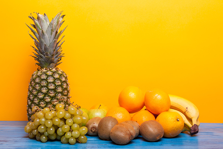 Mixed tasty fruit composition set on yellow background. Fresh healthy summer fruits