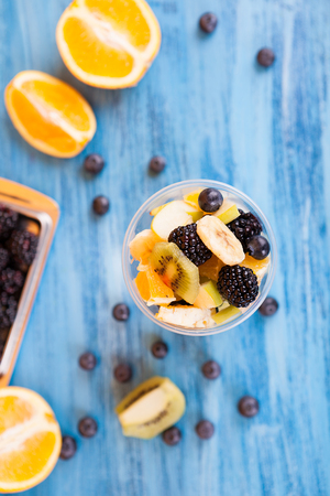 Top view of a cup full of tasty fruits in a cup . Berry, banana orange on wooden table