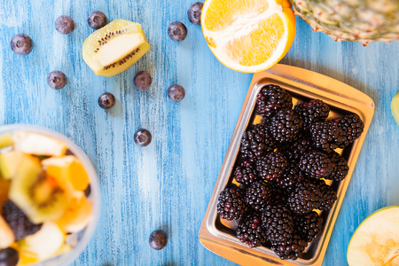 Top view of a cup full of delicious fruits over a wooden desk. Berry, banana, kiwi and grapes over blue table