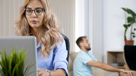 Freelancer woman working on the computer laptop in the house while the husband is watching TV in the background Imagens