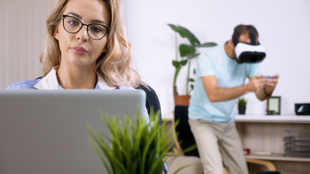 Tired and upset freelancer woman working on the computer laptop in the house while her husband is disturbing her by playing video games with a VR headset in the background.