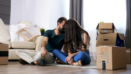 oung couple moving in new home.Sitting on floor and relaxing after unpacking
