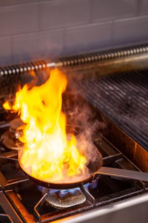 Chef making great flambe beef in restaurant kitchen