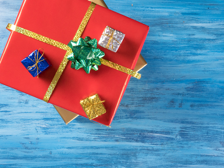 Big red Christmas gift box with smaller boxes on blue vintage wooden background. Celebration symbol.