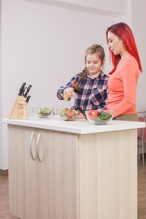 Mother telling her daughter how much oil the salad should have. Oil bottle.