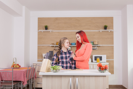 Mother showing affection to her daughter while cooking brunch. Фото со стока