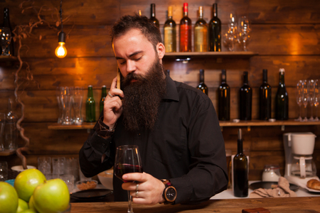 Bartender behind the counter enjoying a glass of wine and talking on the phone. Stockfoto