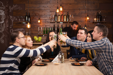 Happy friends group drinking beer and eating pizza at bar restaurant. They are sitting at a wooden table. Banco de Imagens