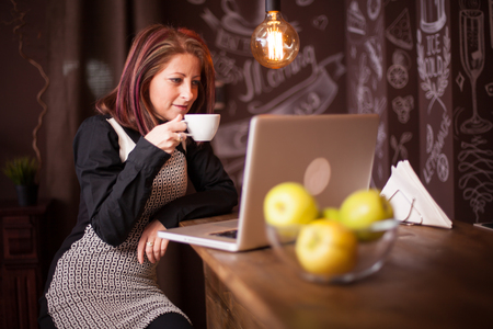 Entrepreneur woman enjoying her coffee in front of her laptop. Relaxing in a vintage coffee shop