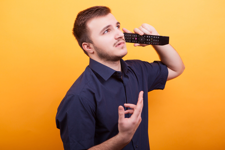Young man acting silly talking on tv remote like is a phone. Young man being funny Foto de archivo