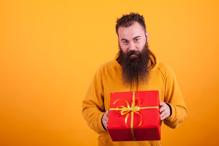 Smiling bearded man looking at the camera and holding a red gift box over yellow background. Standard-Bild