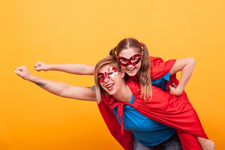 Mother and daughter dressed like superheros flying off to save the world from villans