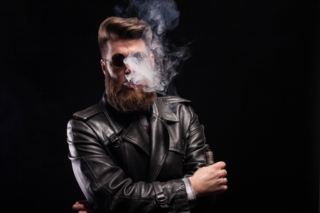 Stylish bearded man in leather jack smoking electronic cigarette over black background. Attractive man. Handsome man.