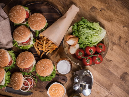 Top view of various fast food on a wooden table. Beef meat. Fresh tomates. Great food. Banco de Imagens