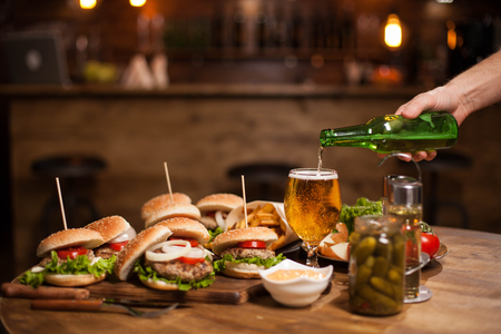 Man hand pours larger beer in a glass standing on a vintage table .Blurred counter bar . Jar of pickles. Stock fotó