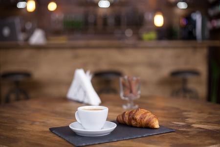 Coffee drink served with croissant on wooden table. Coffee aroma. Tasty croissant. 免版税图像