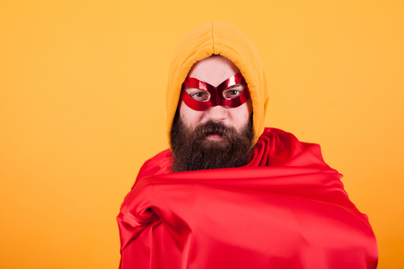 Bearded superhero with red mask showing his red cape over yellow background. Handsome superhero. Banque d'images