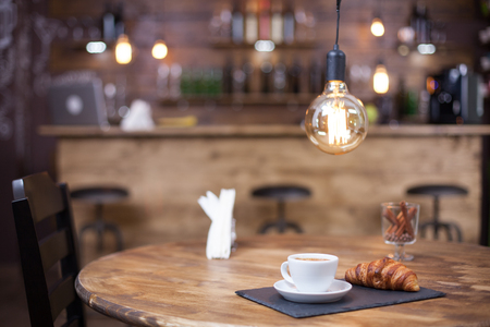 Parisian coffee shop style with tasty coffee served on wooden table. Coffee shop design. 免版税图像