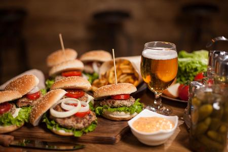 Beste happy hour hamburgers met koud biertje op de houten tafel van een restaurant. Franse frietjes. groene sla.