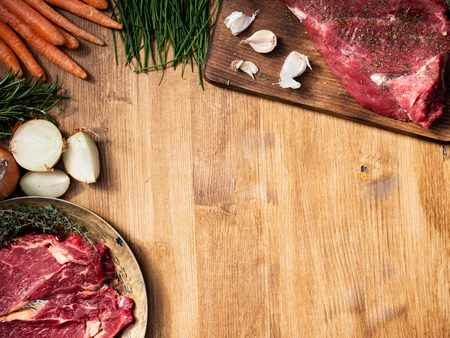 Chopping cutting kitchen board with a big chunk of red meat on it Copy space. White onions. Garlic. Natural protein. Standard-Bild - 119072621