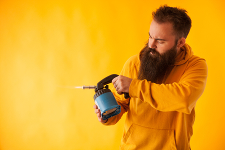 Bearded handy man holding blow torch over yellow background. Professional tool . Blue tool Stock Photo