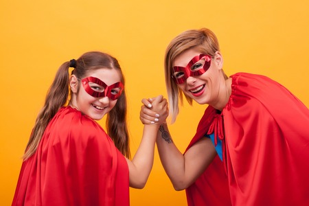 Mother and daughter dressed like superheroes playing arm wrestling and looking at the camera over yellow background. Super mom. Super daughter. Red cape. Red mask. Parenting.