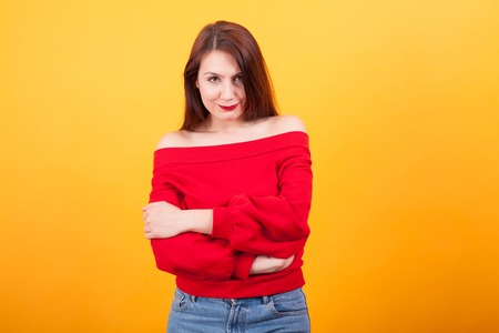 Attractive caucasian woman keeping her arms crossed over yellow background. Smiling at camera. Pretty girl. Charming young woman.