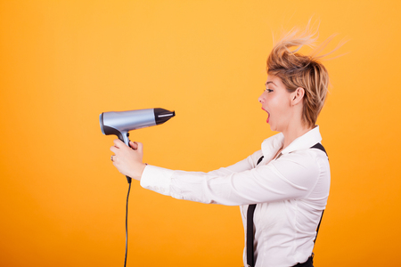 Beautiful young woman with blonde short hair using hairdryer over yellow background.. Hair care. Funny coiffure. Banque d'images